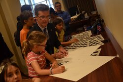 Signing the special gift Chess for Dialogue chess boards by children and permanent representatives.
