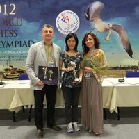 Igor Lobortas and Elena Kadyrova are handing over the cup to Hou Yifan.